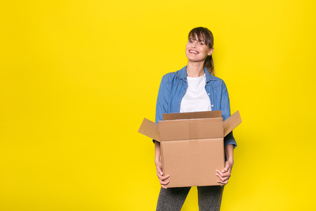 pretty woman standing on yellow background with moving cardboard box Banque d'images