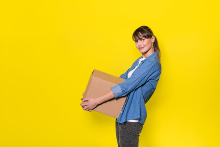 pretty woman standing on yellow background with moving cardboard box 免版税图像