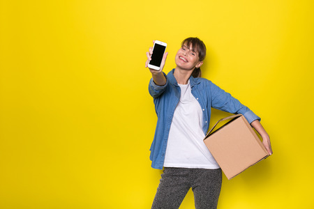 pretty woman standing on yellow background with moving cardboard box and using her cellphone Stock Photo