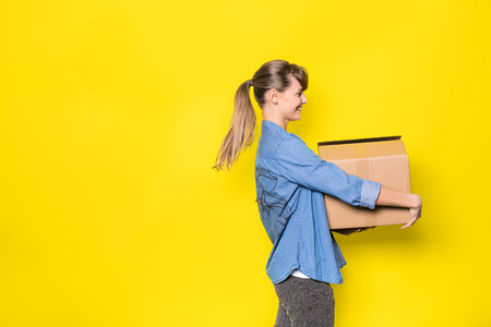 pretty woman standing on yellow background with moving cardboard box Stock Photo