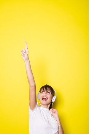 young and beautiful woman  with white headphones pointing up isolated on yellow background