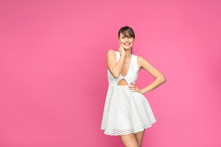 young and pretty woman posing and smiling in white summer dress on pink background Foto de archivo