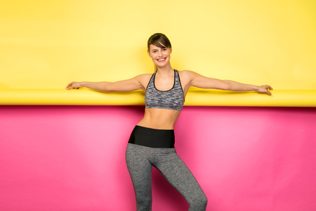 Sport. Fitness woman with athletic body and grey sport outfit on pink and yellow background