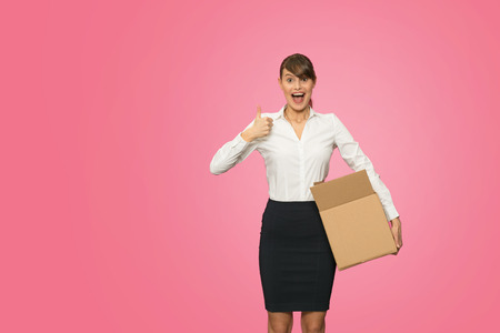very happy beautiful young businesswoman in office outfit resigning her job and carrying her stuff in an cardboard box Stock Photo