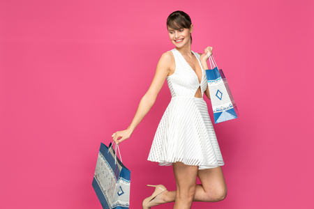 very happy woman in white sexy dress with shopping bags on pink background