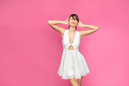 young and pretty woman in white summer dress on pink background, covering her ears