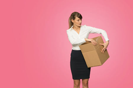 beautiful young businesswoman in office outfit resigning her job and carrying her stuff in an cardboard box Stock Photo