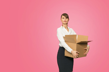 beautiful young businesswoman in office outfit resigning her job and carrying her stuff in an cardboard box Фото со стока