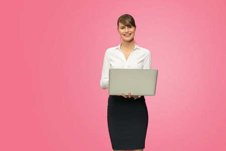 beautiful young businesswoman checking the statistics on laptop, isolated on pink background