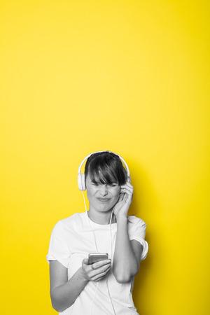 Junge und schöne Frau , die Musik mit weißen Kopfhörern auf gelbem Hintergrund lokalisiert auf Weiß hört Standard-Bild - 95129781