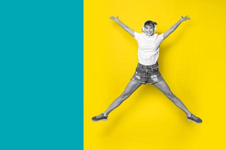 Junge und glückliche Frau Musik hören und springen mit großen Lächeln auf gelbem Hintergrund Standard-Bild - 95129806