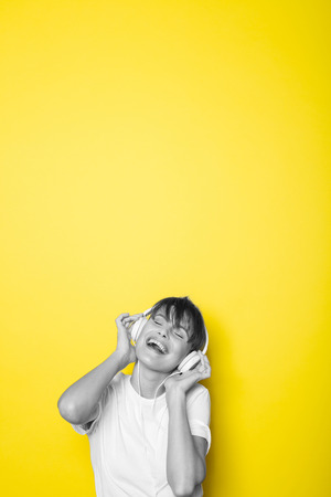 young and beautiful woman listening music with white headphones on isolated on yellow background