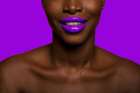 concept of colors with close up of a black skin afro woman mouth smiling with mauve lipstick and background