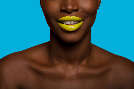 concept of colors with close up of a black skin afro woman mouth smiling, having yellow lips and blue background