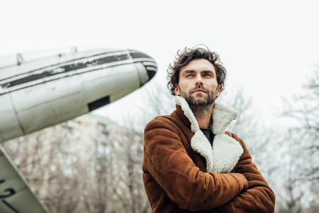 masculine and confident man, in an pilot jacket, standing outside with an old airplane behind