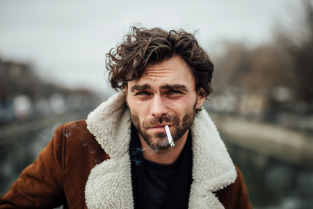 cool handsome man smoking cigarette outside in a aviator coat with masculine attitude waiting for some