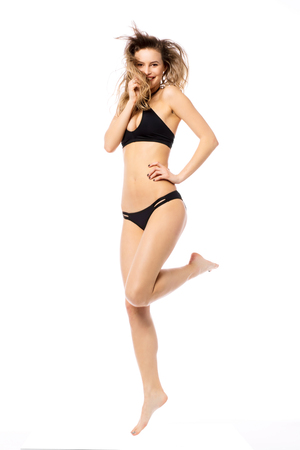 Studio shot of a young woman in a bikini isolated on white jumping with joy and big smile Stock Photo