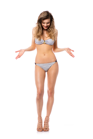Studio shot of a young woman in a bikini isolated on white looking enthusiastic at her body