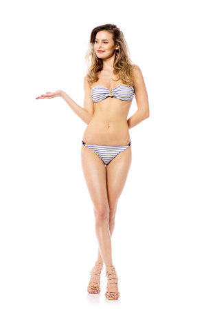 Studio shot of a young woman in a bikini isolated on white presenting with joy one side or one product with her hands
