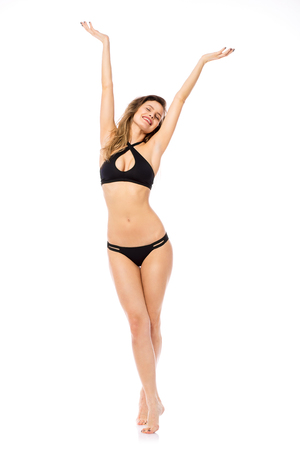 Studio shot of a young woman in a bikini isolated on white standing on peaks with hands up in the air Stock fotó