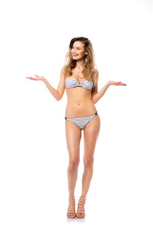 Studio shot of a young woman in a bikini isolated on white presenting with joy one side or one product with her hands and looking to one side