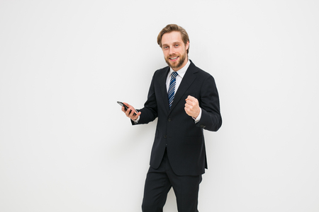 elegant blonde man with beard in suit, with mobile phone in his hand very happy with a win or good news, smiling at the camera on a white wall, successful businessman