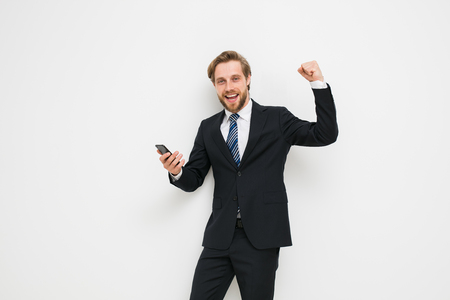 elegant blonde man with beard in suit, with mobile phone in his hand very happy with a win or good news, smiling at the camera on a white wall, successful businessman with fist up