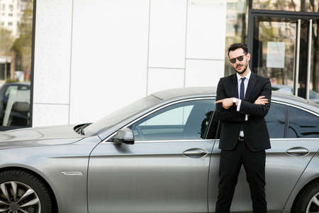 elegant businessman standing outside with folded arms, private driver waiting for his boss pointing limousine Archivio Fotografico