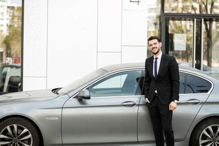 elegant and successful man standing outside with his expensive car ready for driving Stockfoto