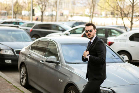 elegant and successful businessman going to a meeting, just steping out from his luxury limousine