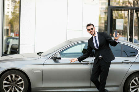 uber driver in elegant suit in front of an luxury car showing his cellphone, outside on the street in front of an office building