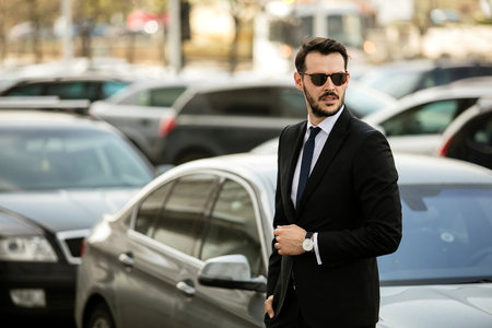 confident successful man with sunglasses outside on the street with expensive car behind him