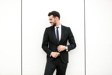 elegant man in suit, businessman, presenter, standing on white wall interacting with free space aroiund him, presenting something Imagens