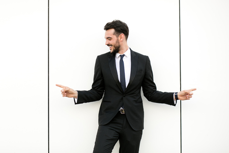 elegant man in suit, businessman, presenter, standing on white wall interacting with free space aroiund him, presenting his sides with big smile, promotion