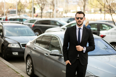 successful elegant man with sunglasses and stylish suit standing in front of his limousine and looking with confidence Stock Photo