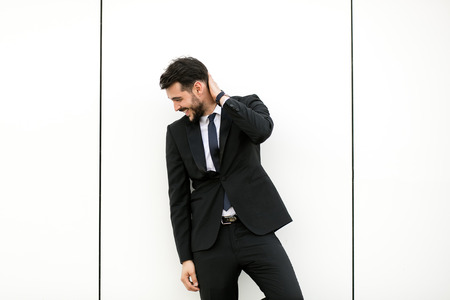 elegant man in suit, businessman, presenter, standing on white wall interacting with free space aroiund him, presenting something Banco de Imagens