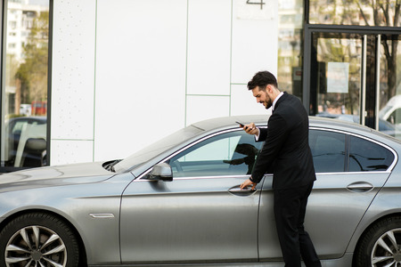 busy elegant man talking at cellphone while steping into his expensive car