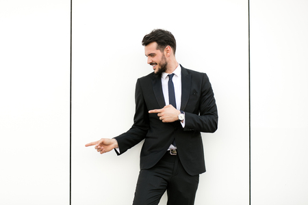 elegant man in suit, businessman, presenter, standing on white wall interacting with free space aroiund him, presenting his side with joy