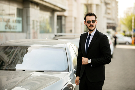 elegant man in suit, successfull businessman standing next to his limousine and looking with confidence