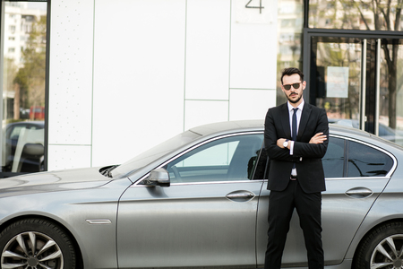 elegant businessman standing outside with folded arms, private driver waiting for his boss in front of luxury limousine