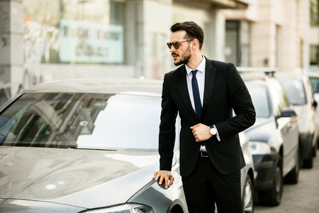 confident elegant man in suit with sunglasses, steping into his luxury car, on the street of a city