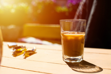 glass of ice coffee outside on a table in the sun Stock Photo