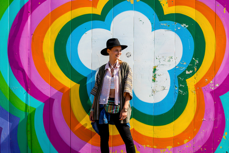 young girl with hat, hipster and traveler, smiling and enjoying life and freedom, standing in middle of flower colorfull rainbow