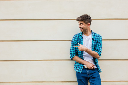 handsome man in checkered shirt smiling standing outside leaning on a wall with free space next to him pointing the empty area