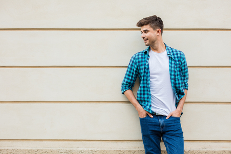 handsome man in checkered shirt smiling standing outside leaning on a wall with free space next to him, looking to empty are