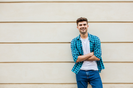 handsome man in checkered shirt smiling standing outside leaning on a wall with free space next to him