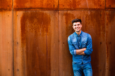 cheerful young man, cool guy in jeans outfit, looking with joy and smile to camera and pointing the empty space around him, are for text or product, on a rusty background Banco de Imagens