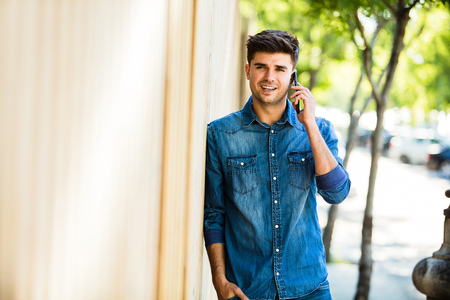 young man in jeans outfit talking at mobile phone and smiling, outdoor, on the street against a wooden background