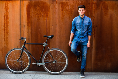 a fashionable guy in jeans outfit next to his single speed bike on a rusty background Stockfoto