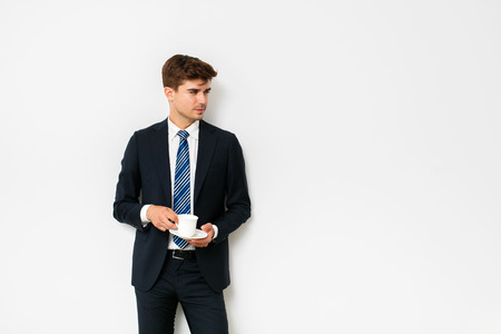 elegant man in suit, office businessman, drinking a coffee on white background, recovering after a hard night or starting a new day